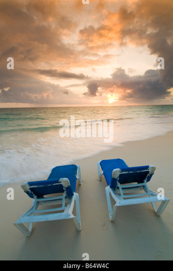 Caribbean Dominican Republic couple of lounge chairs on beach at sunrise in front of all inclusive resort - Stock-Bilder