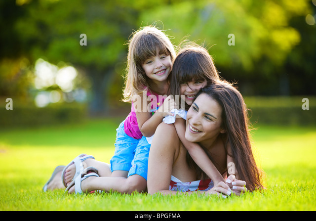 Young mother and two daughters playing in grass - Stock Image