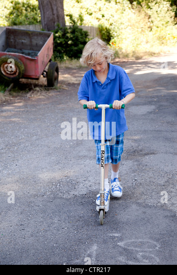 Boy outside playing on his scooter. - Stock Image