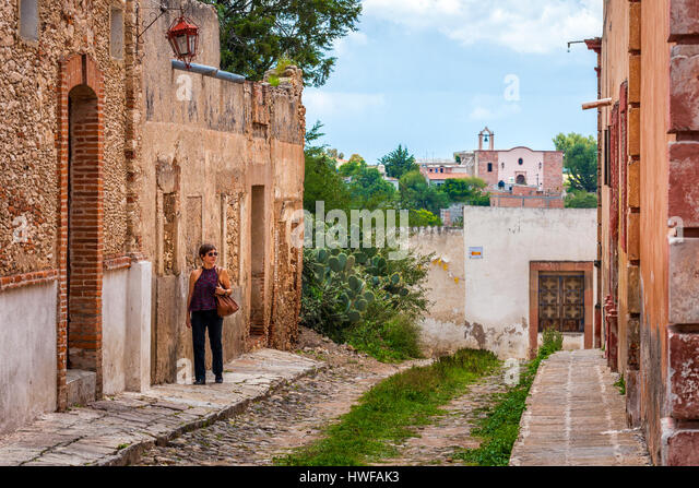 Middle aged female tourist strolls the streets of colonial Mineral de Pozos, Guanajuato, Mexico. - Stock Image