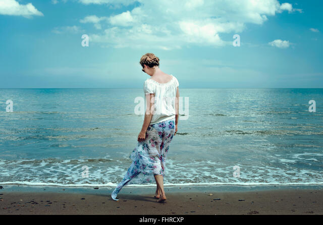 young woman walking on the beach - Stock Image