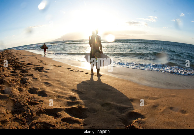 Two men walking on the beach with skimboards in search of the right spot in nice light. - Stock Image