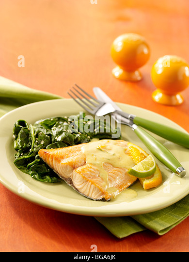 Baked salmon with citrus yogurt sauce and spinach - Stock Image