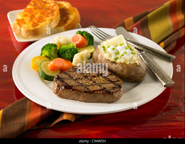 Top Sirloin steak with a loaded baked potato, vegetables and garlic bread - Stock Image