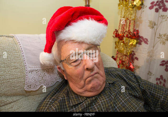 Lonely old age pensioner in his eighties asleep during Christmas Day celebrations on his own, England, UK - Stock Image