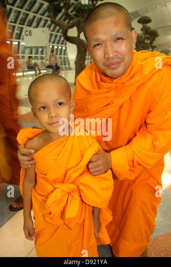 Bangkok Thailand Suvarnabhumi International Airport BKK terminal concourse gate area Buddhist Asian man monk robe - Stock Image