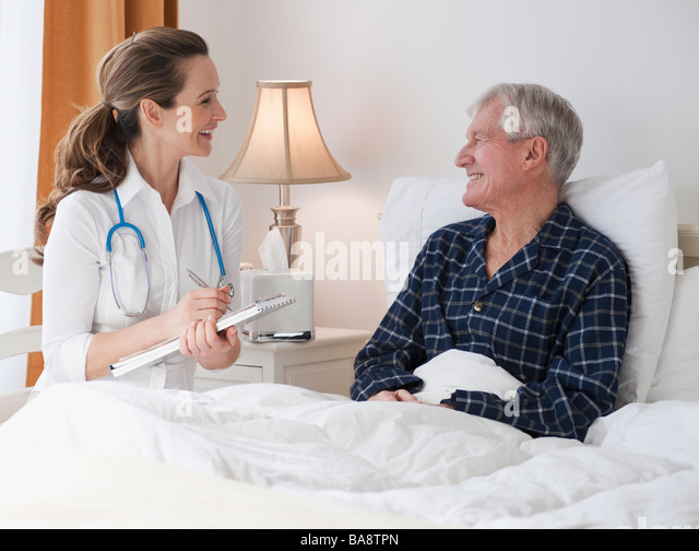 Nurse caring for senior man in bed - Stock Image