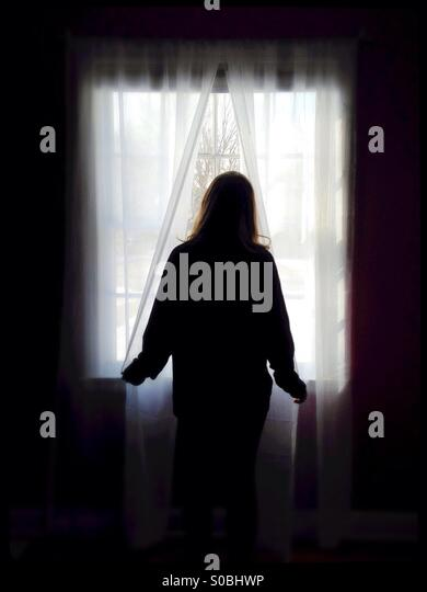 A woman standing at a window, looking out. - Stock Image