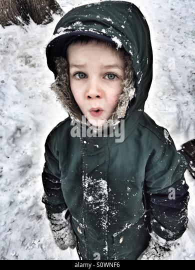 Young boy in a parka outside in the snow in winter time - Stock Image