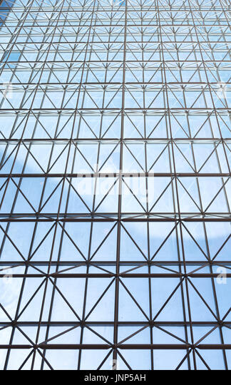Contemporary steel structure and transparent glass roof revealing blue sky with light clouds - Stock Image