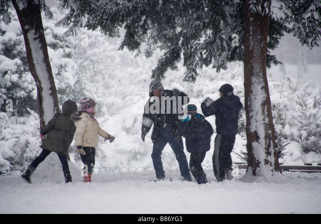 Winter children park playing snowball fights - Stock Image