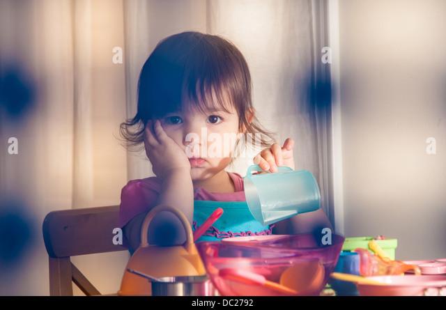 Sad girl playing with toys - Stock Image