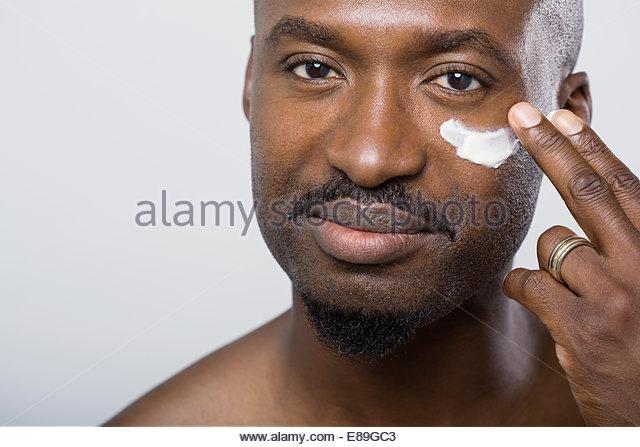 Close up of man applying moisturizer under eye - Stock Image