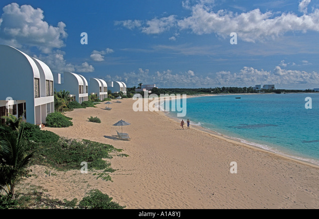 Anguilla beach water couple deserted beach Covecastles Resort idyllic iconic caribbean beach scene on Shoal Bay - Stock Image