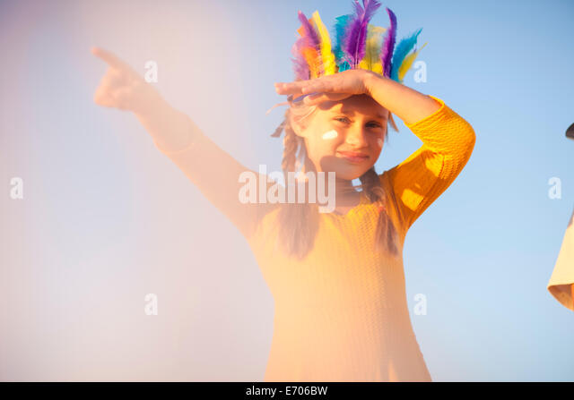 Girl dressed as native american in feather headdress with hand shading eyes and pointing - Stock Image