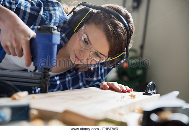 Girl with drill woodworking in garage - Stock Image