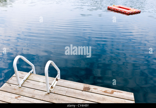 Dock and ladder on calm summer lake with diving platform in Ontario Canada - Stock Image