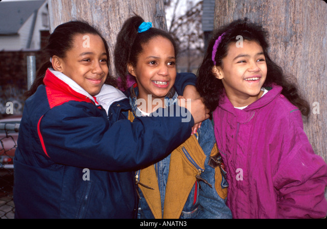 New Jersey Paterson Black girls friends hug look smile - Stock Image