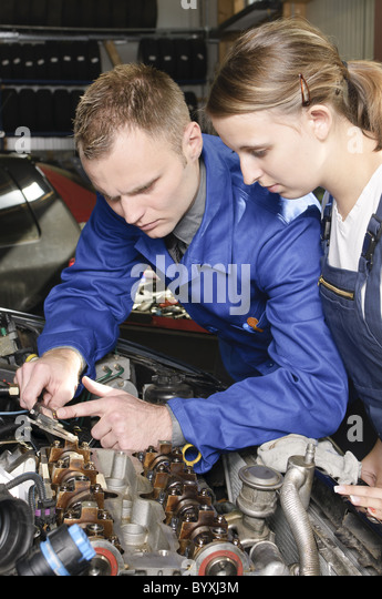Apprentice and master in garage - Stock Image