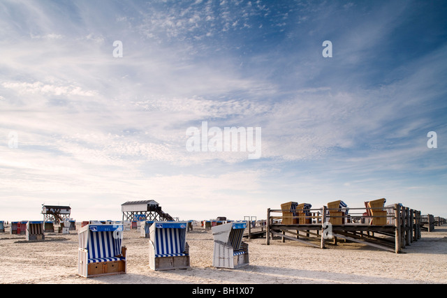 Beach chairs on the beach under clouded sky, St. Peter Ording, Eiderstedt peninsula, Schleswig Holstein, Germany, - Stock Image