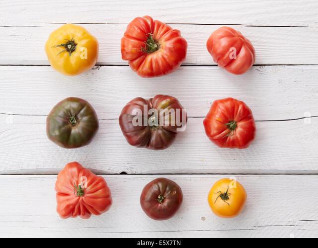 Arrangement of nine heirloom tomatoes - Stock Image