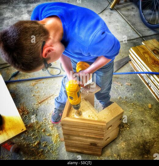Young boy drills a hole in a wooden birdhouse - Stock Image