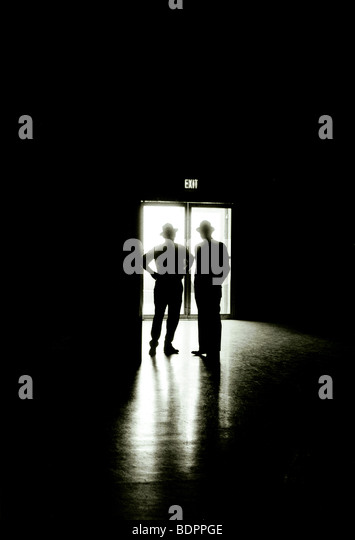 Two male figures silhouetted against an exit doorway - Stock-Bilder