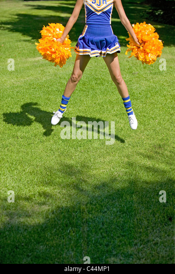 cheer leader jumping shows head cut off - Stock Image