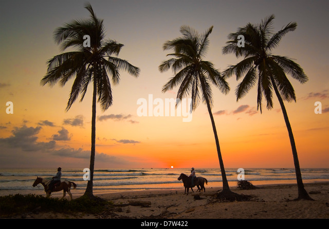 Horse riders at sunset, Playa Guiones surfing beach, Nosara, Nicoya Peninsula, Guanacaste Province, Costa Rica - Stock Image