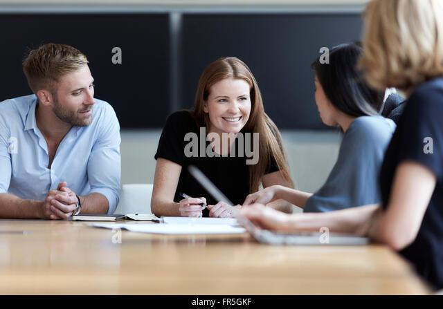 Smiling business people talking in meeting - Stock-Bilder