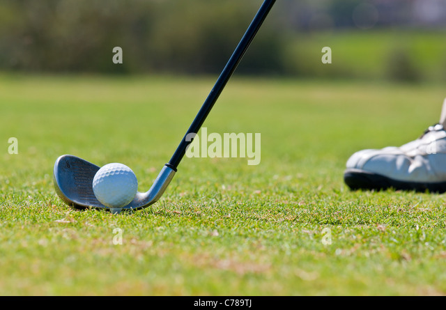 A real golfer in a golf course getting ready to strike the ball. - Stock Image