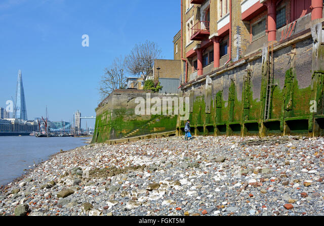 Wapping & River Thames foreshore at low tide shows old base walls of  riverside warehouse buildings with Tower - Stock Image