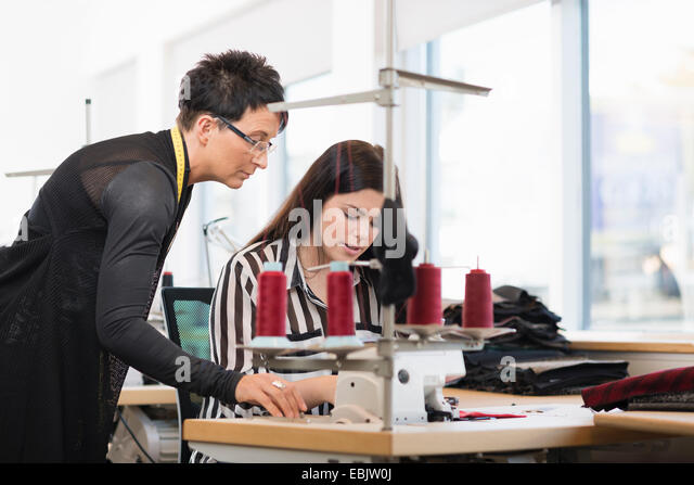 Two seamstresses looking down at sewing machine in workshop - Stock-Bilder