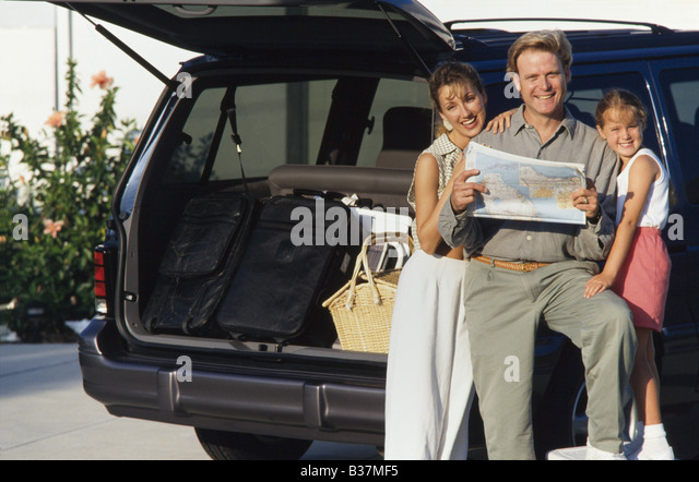 Family packing minivan with luggage, checking maps, Miami - Stock Image