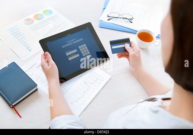 Successful businesswoman inputting login information to carry out online banking operation on digital tablet in - Stock-Bilder