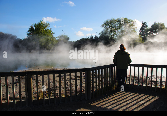 A young woman admiring the  steaming ponds in Taupo town centre, New Zealand - Stock Image