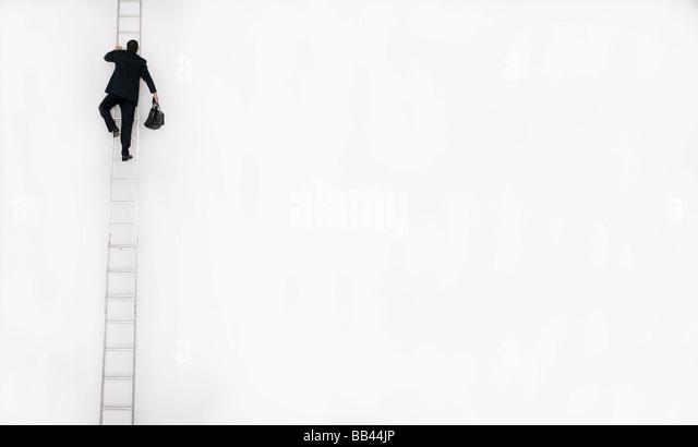 Man in business suit climbs a tall ladder, San Diego, California. - Stock-Bilder
