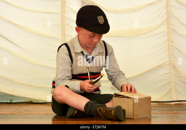 Naughty School Boy in 1940 taken his catapult out of his gas mask box - Stock Image