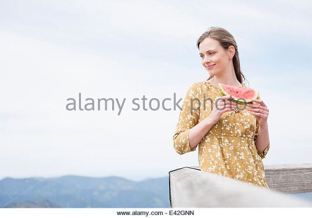 Mid adult woman eating watermelon, Wallberg, Tegernsee, Bavaria, Germany - Stock Image