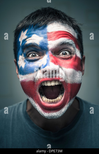 Portrait of angry man with USA flag painted on face. - Stock Image
