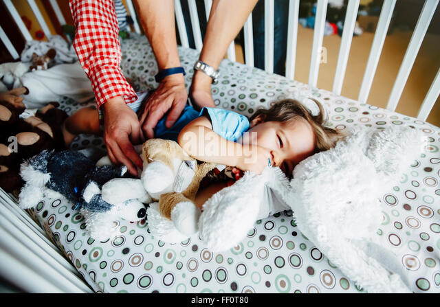 Gay fathers tickling baby son in crib - Stock Image
