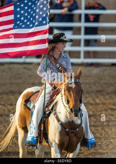 Rodeo Queen carrying American Flag on horseback during National Anthem, Chaffee County Fair & Rodeo, Colorado, - Stock-Bilder