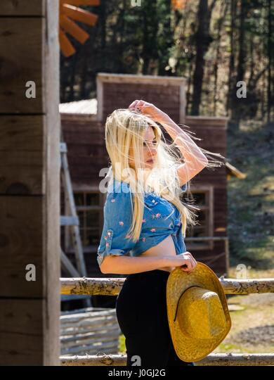 Attractive beautiful blonde young woman blowing wind windy - Stock Image
