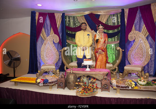 Bangladeshi bride  and groom at their wedding reception waiting to greet their families & guests in Brooklyn, - Stock Image