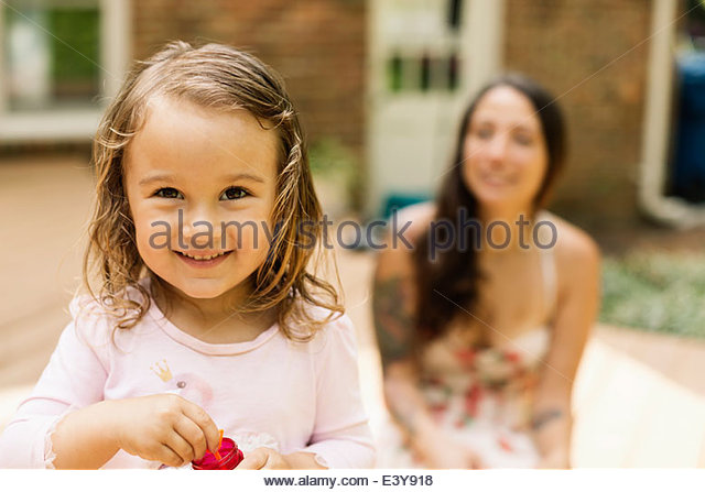 Portrait of female toddler with mother blowing bubbles in garden - Stock Image