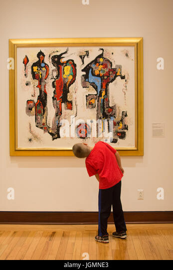 A 10-year old boy inspects a colorful painting of Western art at the Rockwell Museum in Corning NY - Stock Image