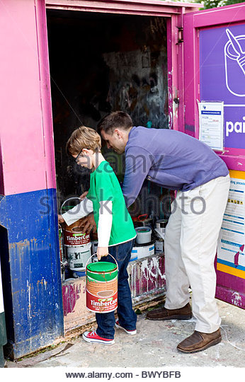 A father and son recycling tins of paint - Stock Image