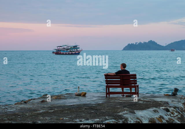 Lonely man sits on a bench on the coast looking at the sea. - Stock Image