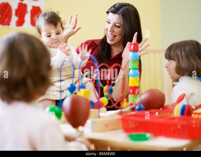 female toddler and 2-3 years girl playing in kindergarten. Horizontal shape - Stock Image