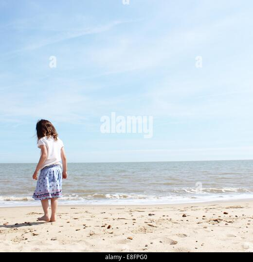 Rear view of girl standing on beach - Stock Image